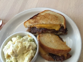 Deluxe grilled cheese with bacon, grilled onions, and tomato jam and potato salad