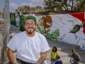 Chacho Lopez is all smiles as he sits in front of the completed mural.