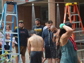 Participants hose off with the Milwaukee Fire Department after the tomato fight