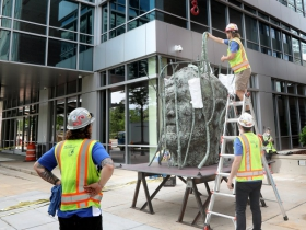 Workers install piece by Jim Dine