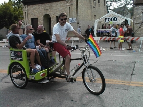 Joe Pabst and friends cruise through the Pride Parade aftermath on a chauffeured bicycle. It's the way to go for special occasions like this.
