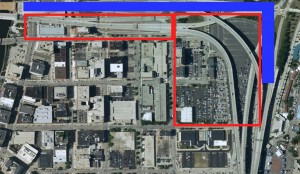 The red-framed land is the land that would made available for redevelopment as a result of the bridge reconfiguration.  The blue illustrates the street-level boulevard that would replace the elevated freeway.