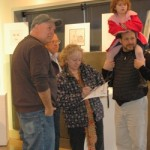 Gallery 2622 owner John Korom (baseball hat) discusses the show with art patrons