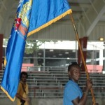 A Milwaukee athlete carries the state flag.
