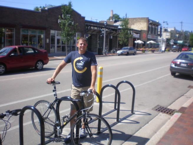 Chris Socha of The Kubala Washatko Architects, Inc. trying out the new bike corral at Cafe Hollander