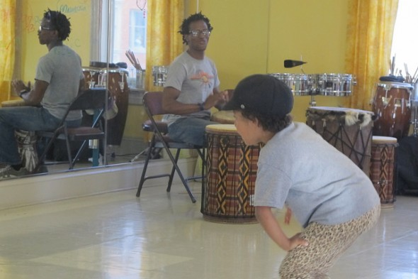 "Walker's Point Center for the Arts musician ""Souljah"" beats the Djembe drum as young people practice African Ameri-dance. (Photo by Edgar Mendez)"