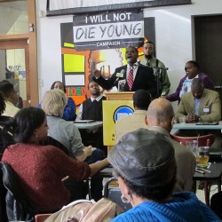 """Poet Kwabena Antoine Nixon addresses the audience at the """"I Will Not Die Young"""" event at the Coffee Makes You Black coffee shop."""