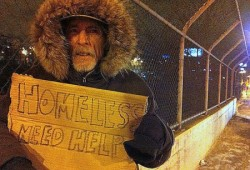 David Marble, a homeless man, holds a sign asking for help from motorists. (Photo by Brendan O'Brien)