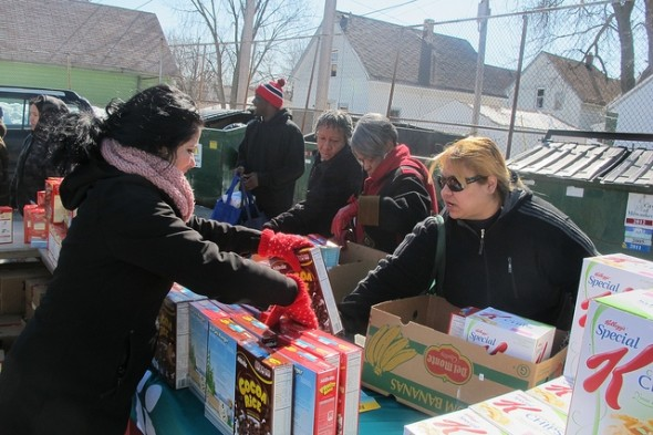 Alexandria Alvarado of Molina Health Care hands out cereal to residents. (Photo by Edgar Mendez)