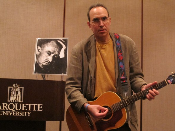 """Author-Actor-Educator Paul McComas performs Bruce Springsteen's stirring """"The Ghost of Tom Joad,"""" inspired by """"The Grapes of Wrath."""" To his right is a photo of John Steinbeck. (Photo by Jennifer Reinke)"""