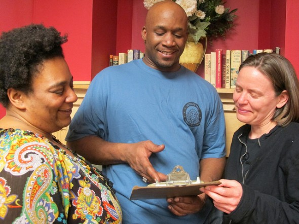 Danell Cross, Metcalfe Park Community Action Team (MPCAT) co-captain; Duril White, MPCAT co-captain; and Debbie Davis, Milwaukee Area Time Exchange executive director, look over a sign-up sheet at a recent potluck dinner. (Photo by Jennifer Reinke)
