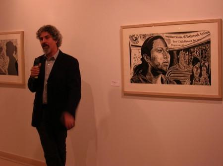 Raoul Deal tells the story behind his woodcut prints at Latino Arts Inc. (Photo by Amalia Oulahan)