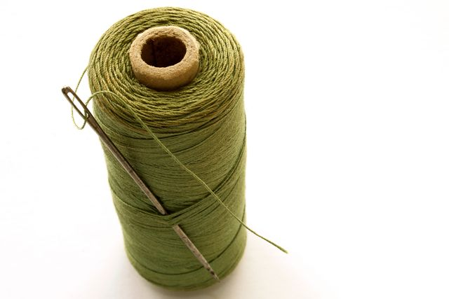 Reel of green cotton with threaded needle