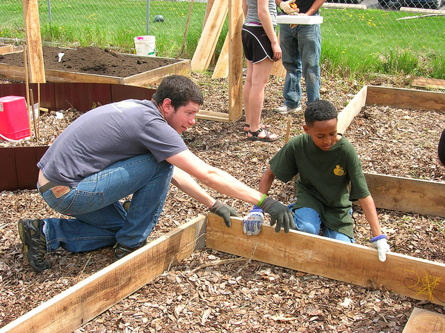 Two volunteers fit together the lumber for a raised garden bed. (Photo by Amalia Oulahan)