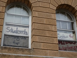 Protesters display signs from the windows of Bascom Hall while occupying a reception area outside interim Chancellor David Ward's office on April 29. Bill Lueders/Wisconsin Center for Investigative Journalism