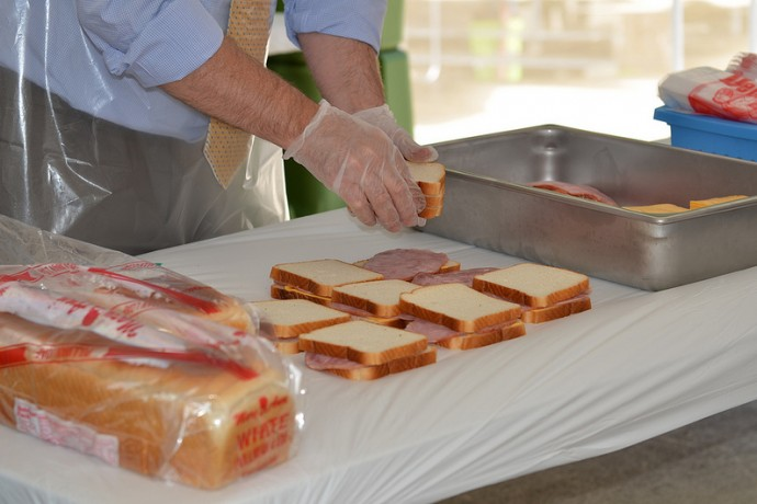 Volunteers and community leaders make sandwiches at the kickoff event at Red Arrow Park. (Photo by Sue Vliet)