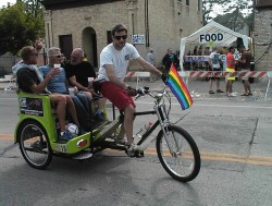 Joe Pabst and friends cruise through the Pride Parade aftermath on a chauffeured bicycle. It's the way to go for special occasions like this. Photo by Michael Horne.