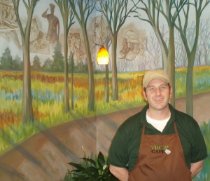 General Manager Chris Kadrich is backed by a mural donated by artist Colleen Drew, visually describing the path veterans take from active service to their return home. Photo by Peggy Schulz.