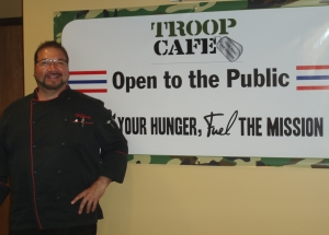 """Greg Bautista, Head Chef, helps promote Troop Café's slogan: """"Feed Your Hunger, Fuel The Mission."""" Photo by Peggy Schulz."""