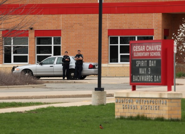 Police stand guard outside a Madison school, which went into lockdown May 2 along with schools in Verona, during a manhunt for a fugitive from Chicago. School districts are increasingly looking to new technology to contact parents in such emergencies -- and in the fall, Verona will begin automatically signing parents up for text alerts and other emergency communications. Amber Arnold/Wisconsin State Journal