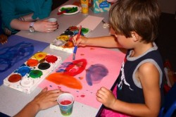 Aidan, a camper, paints a fish during craft time. (Photo by Maggie Quick)