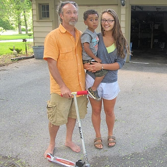 Rick Kohen and his daughter Kaitlyn have begun to teach JJ's 3-year-old son Julius how to ride a scooter. (Photo by Edgar Mendez)