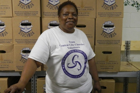 Alicia Ellis, director of Central City Churches, stands in front of boxes of packaged food waiting to be sorted and distributed to needy families. (Photo by: Eric Oliver)