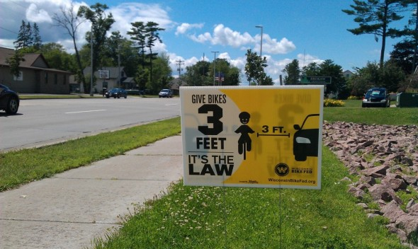 One of our Share and Be Aware yard signs encouraging people to obey the law that requires cars to pass bicycles by 3ft or more.