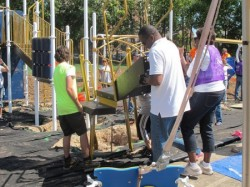 Volunteers assemble climbing accessories for the new playground. (Photo by Shakara Robinson)