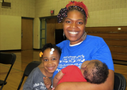Boys & Girls Club Stein Scholar Coordinator and MPS parent Kwan Exum holds her daughter Katora, 5, and son Jrew, 3 months. (Photo by Andrea Waxman)