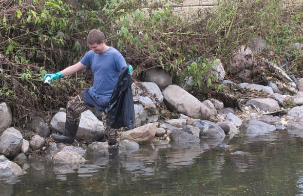 Kyle Puckhaber helped remove trash from the Kinnickinnic River during a clean-up event. (Photo by Scottie Lee Meyers)