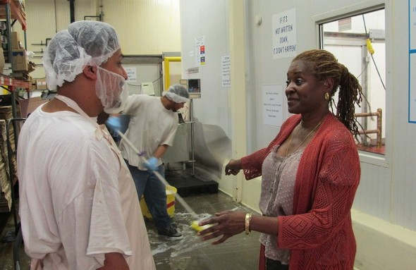 Daphne Jones, owner of Glorious Malone's Fine Sausage, Inc., talks with employee Nick Reynosa at her plant at Martin Luther King Drive and Walnut Street. (Photo by Andrea Waxman)