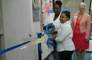 Julie Tolan, CEO of the YMCA of Metropolitan Milwaukee, watches as Faye (left) and Alexis Williams cut the ribbon for the new health care clinic at the Northside YMCA. (Photo by Eric Oliver)