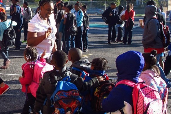 """City Year corps members, teachers and staff greet arriving students with smiles and """"high fives"""" at Carver Academy. (Photo by Rick Brown)"""
