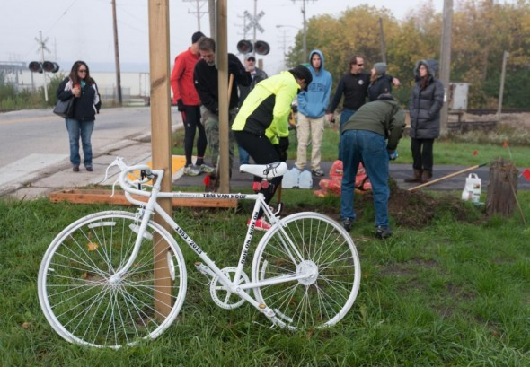 Friends and family members of Tom Van Hoof dig a hole for the concrete foundation where they installed the Ghost Bike at the intersection of the Oak Leaf Trail and Mill Road in Glendale.