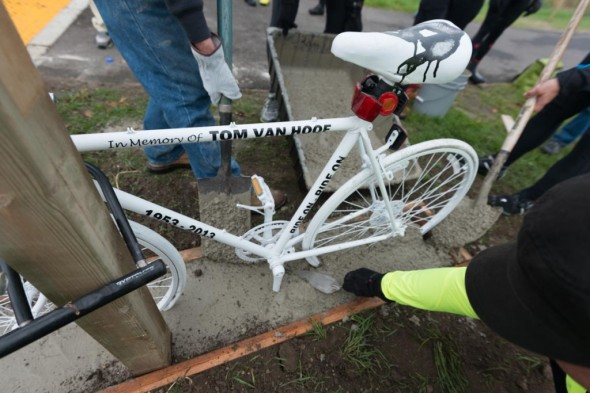 The Ghost Bike is set in a concrete foundation and locked to the trail sign.