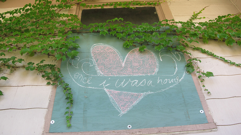 An artist leaves a message on a boarded-up window. (Photo by Scottie Lee Meyers)