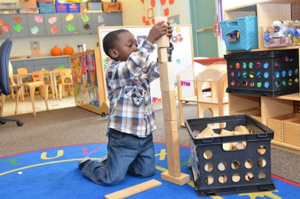 A Head Start student at Next Door Foundation reaches for the sky with his block tower. (Photo by Sue Vliet)