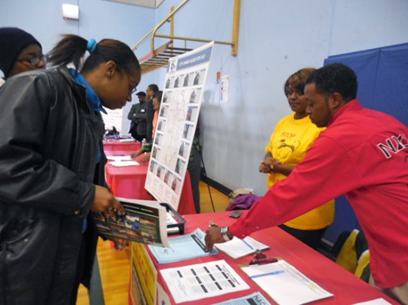 Carisa Houston, 41, receives information from Tory Goodman, mortgage consultant at Neighborhood Assistance Corporation of America (NACA), and NACA member Tanya Harris.
