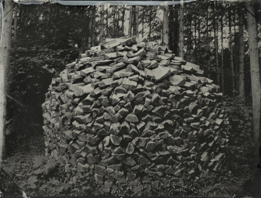 Nick Olsen's photography work uses 19th century methods. For example, this photo of a woodpile is actually an example of tintype photography, printed on a sheet of iron.
