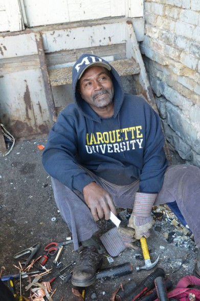 A scrapper uses a hammer to take apart cable containing copper, which he found in a Dumpster downtown. (Photo by Sue Vliet)