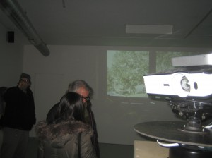 While the fixed projector plays its scene on the north wall of the gallery, the rotating projector spins toward the viewer in this image. Photo by Michael Horne.