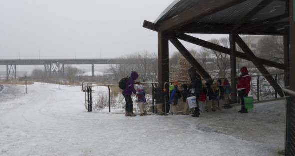 Ten little reasons why the Hank Aaron State Trail should be maintained in the winter. There are classes of little kids who use the trail most every day, all winter long. Here you can see they have to hold the railing and inch along the raised edge of the bridge because the path is iced over.