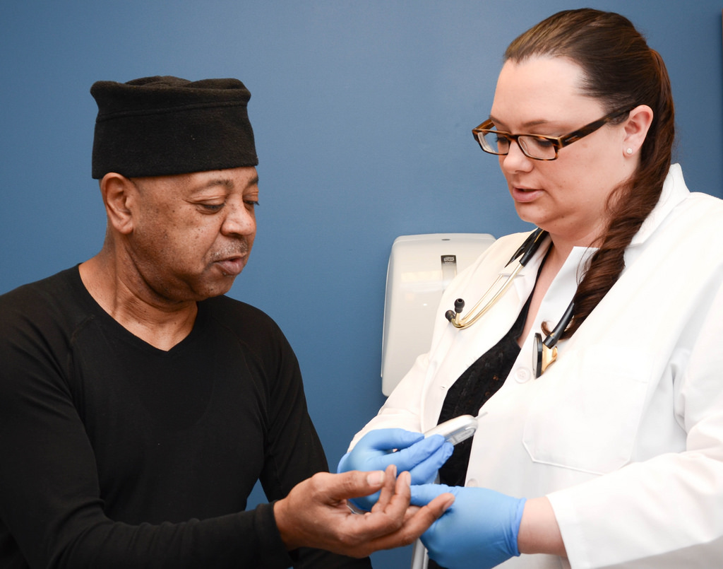 Litisha Ramus, a family nurse practitioner at Milwaukee Health Services' Convenient Care Clinic, tests the blood of patient Tony Driver. Photo courtesy of Milwaukee Health Services.