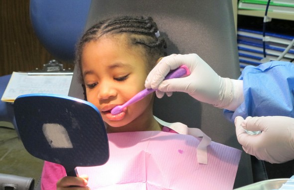 Arielle Williams observes the proper brushing technique demonstrated by Smart Smiles dental assistant Calandria Duncan. (Photo by Andrea Waxman)
