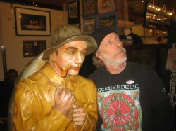 Patrick Nedobeck (right) mugs with the restored fisherman sculpture (left) at St. Paul Fish Company in the Milwaukee Public Market. The pipe-smoking fisherman had spent years in the Smith Bros. Fish Shanty in Port Washington before finding his new home in the Milwaukee Public Market this week.