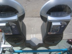 New caps on existing parking meters on E. Brady Street accept coins and plastic. Note bicycle below, signed by Mary Burke. Photo by Michael Horne