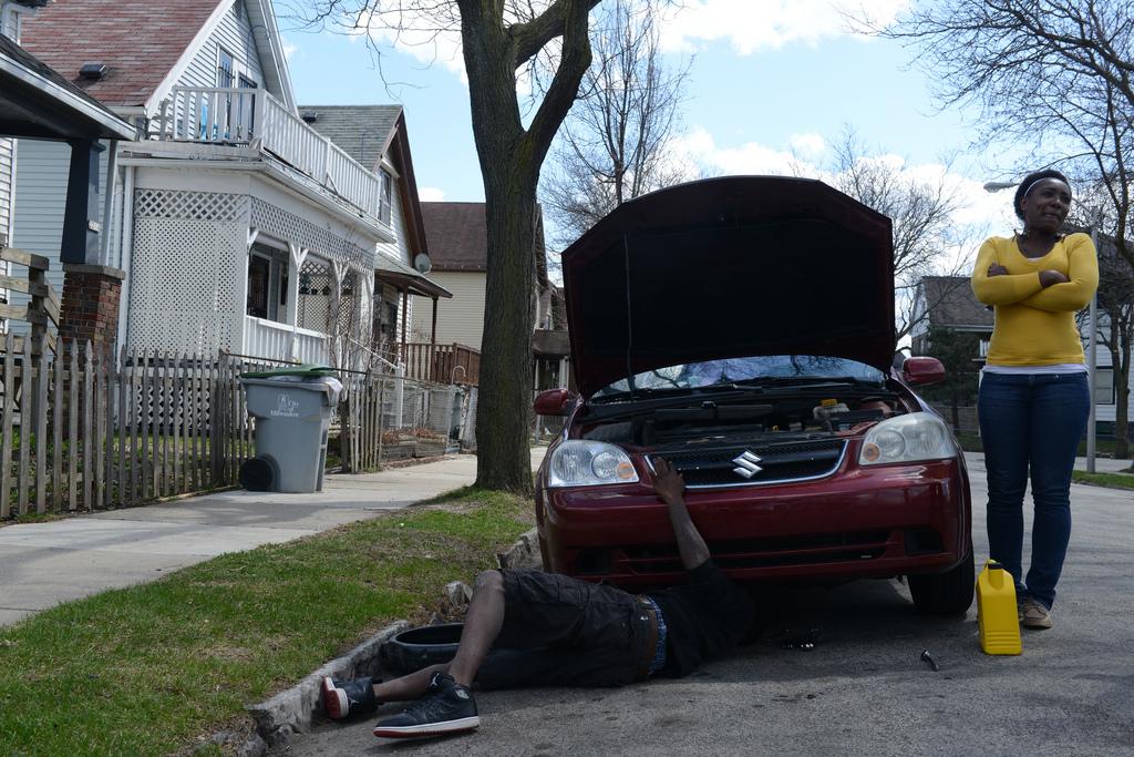 Mitchell Aaron performs auto maintenance on Michelle Taylor's maroon Suzuki sedan. (Photo by Sue Vliet)