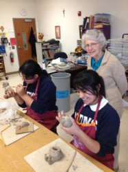 Sister Ellman watches students craft ceramics. (Photo by Henry Greening)