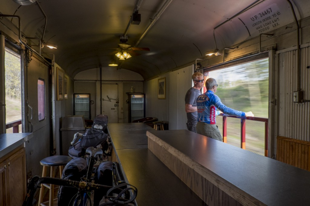 Our bikes ride unboxed ride in the baggage car, where we can watch the scenery speed past through open doors.